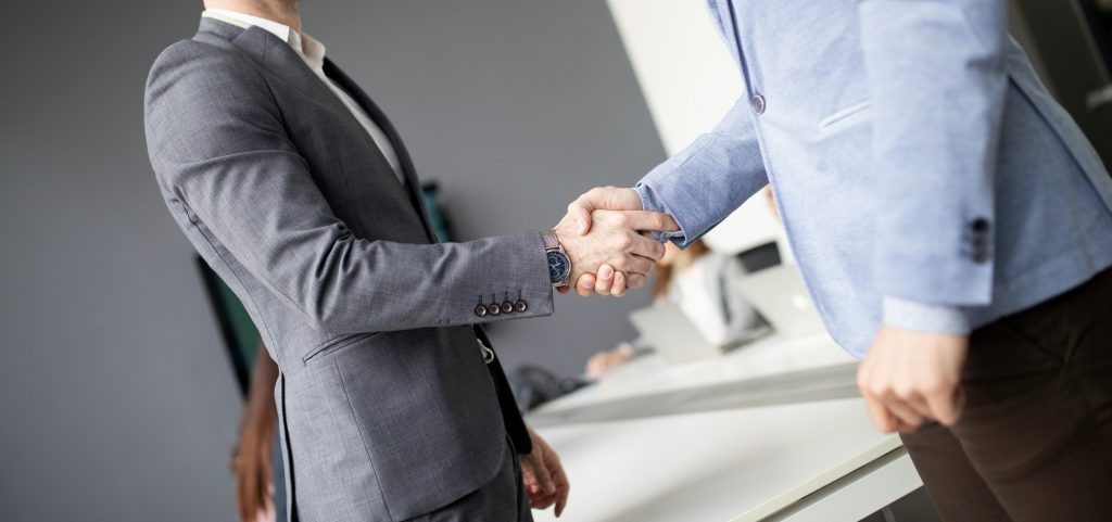 Two confident business man shaking hands during a meeting in the office
